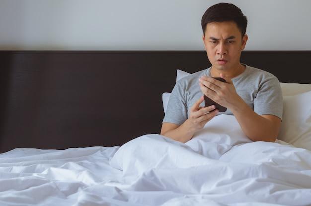 Азиатский человек наблюдая серьезные онлайн новости на умном телефоне в утре на кровати.