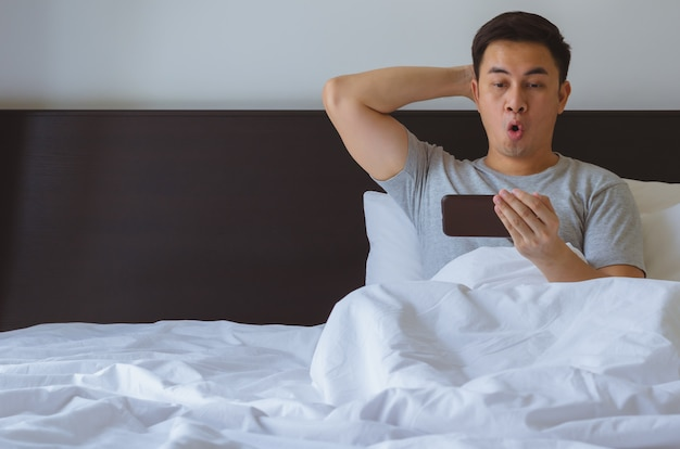 Азиатский человек смотрит сюрприз новости онлайн на смарт-телефон утром на кровати.