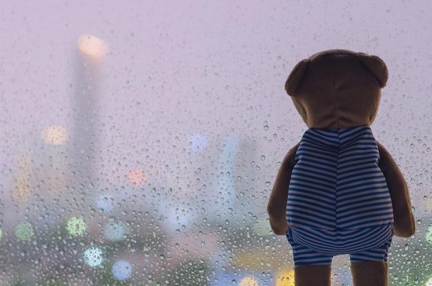 夜雨が降っているときにガラス窓から外を見るテディベア。