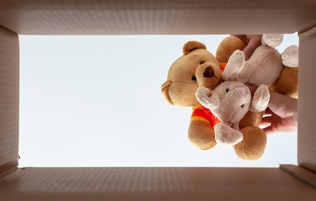Упаковка кукол в коробку для домашнего переезда. фотография занимает от нижней точки зрения.
