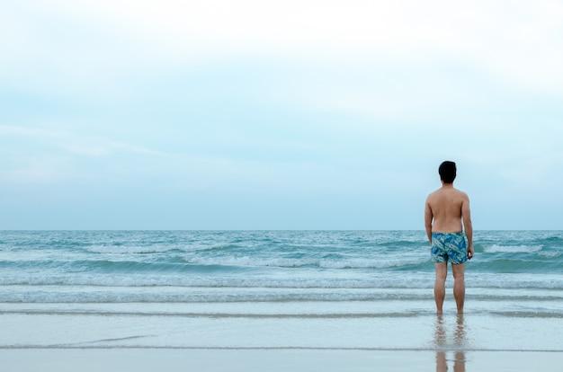 孤独なアジア人男性がビーチで一人で立って