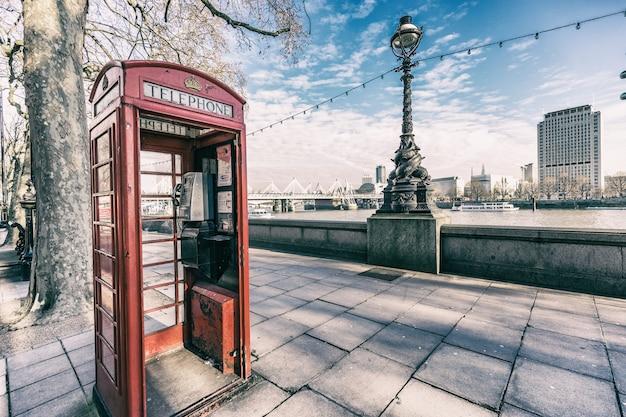 デ・テムズ川の横にあるロンドンの赤いブースの電話