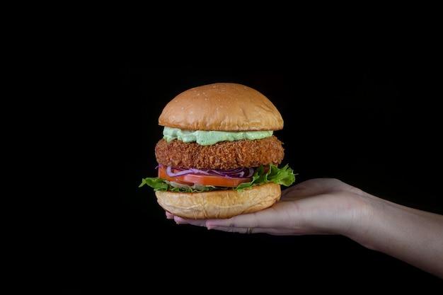 レタス、トマト、紫タマネギ、手作りマヨネーズのチキンバーガーを黒の背景に持つ手。おいしい。