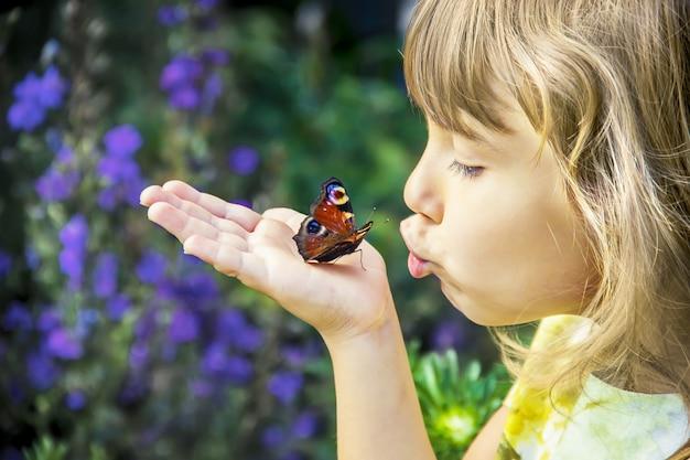 彼女の手に蝶を持つ子供。
