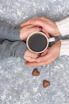 コーヒーのカップを保持している男性と女性の手。セレクティブフォーカス