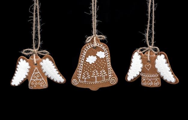クリスマスの手作りのジンジャーブレッドクッキーは、黒の背景にある。