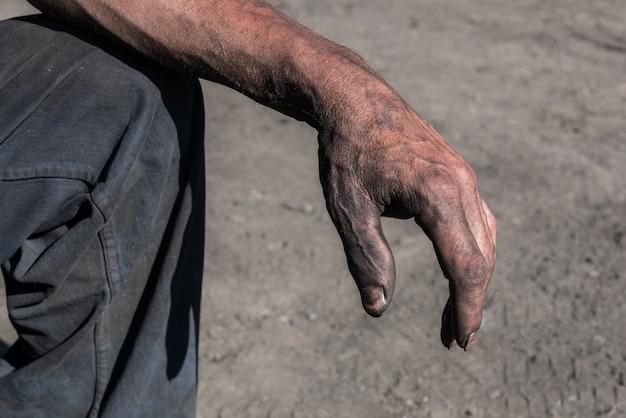 チャコール・バーナー汚れた手を持つ労働者の男。労働者の手。汚れた手を持つ労働者の男。