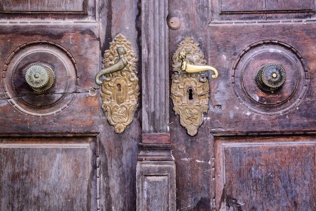 鉄の取っ手が付いている古い木製のドアの前景。木製のドアに古いさびたゲートハンドル。