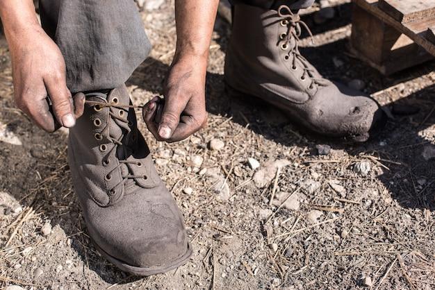 チャコール・バーナー作業員は靴ひも、クローズアップ写真を結びつける。彼女の靴を閉じている労働者の男