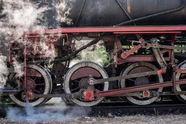 古い機関車の車輪。歴史的な蒸気機関車は落葉樹林を通過します。