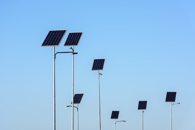 Уличное освещение работает от солнечных панелей на фоне голубого неба.