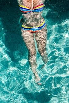 美しい若い女性はプールで泳いでいるとリラックス。