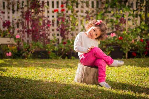 ピンクのズボンの裏庭に座っている魅力的な女の子