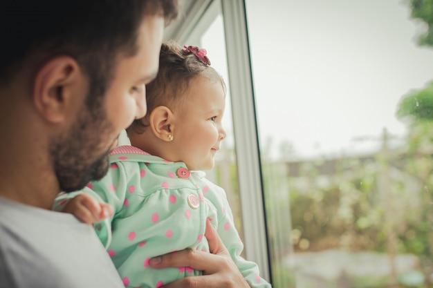 Счастливый отец держит свою очаровательную дочь перед окном