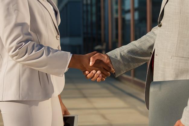 Черная деловая женщина пожимает руку мужскому партнеру