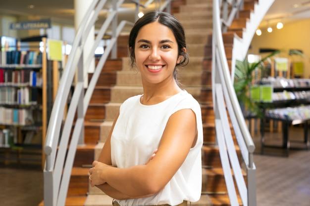 Красивая азиатская женщина представляя на библиотеке