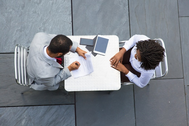 Деловой человек подписывает документы во время встречи с партнером