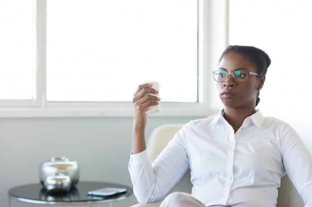 Задумчивый бизнес-лидер наслаждается перерывом на кофе