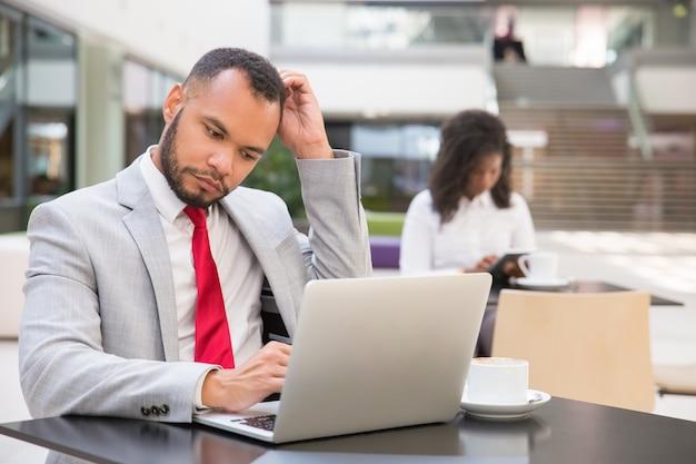Задумчивый мужчина менеджер, используя ноутбук, попивая кофе