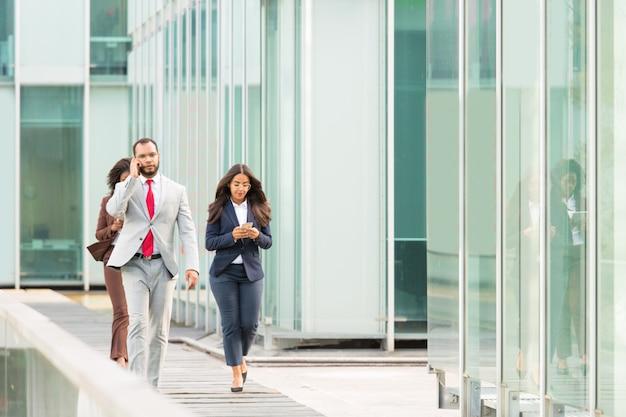 Серьезные бизнесмены с гаджетами идут по городской стеклянной стене