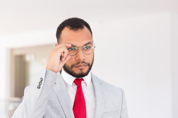 Серьезный бизнес-лидер позирует перед камерой в офисном зале