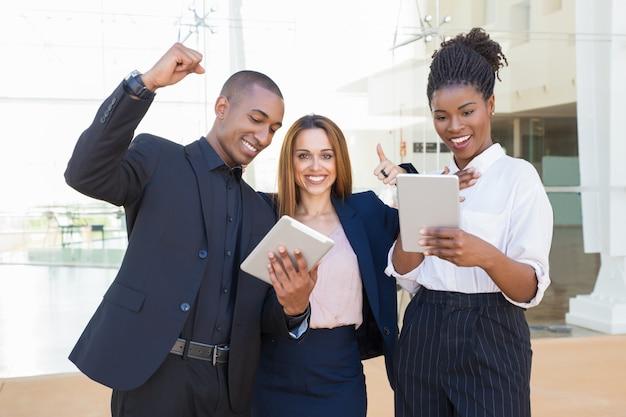 Веселые коллеги по бизнесу с планшетами