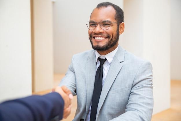 Веселый деловой человек приветствует коллегу