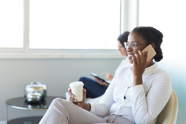 Веселый офисный работник разговаривает по мобильному