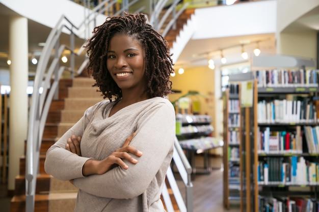 陽気な笑顔の女性が公共図書館でポーズ