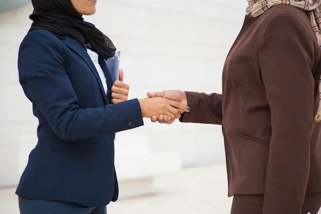 イスラム教徒のビジネスウーマンハンドシェイクのクローズアップ
