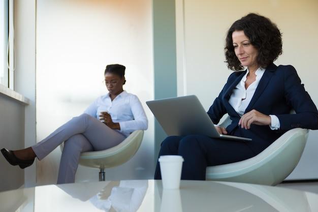 オフィスラウンジでコンピューターに取り組んでいる自信を持ってビジネスリーダー