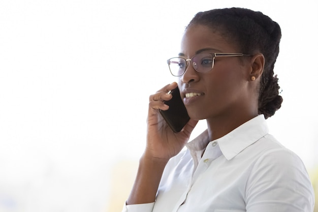Уверенно женщина-консультант разговаривает по мобильному телефону