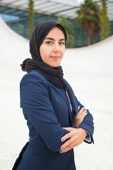 自信を持って誇りに思ってイスラム教徒の実業家が外でポーズ