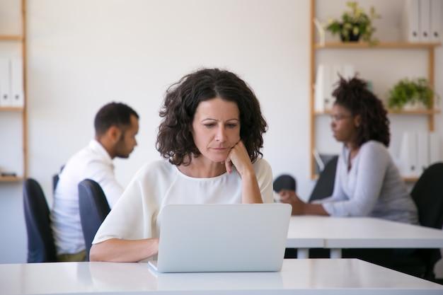Серьезный профессионал, использующий ноутбук в офисе