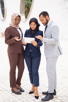 Успешная бизнес-группа смотрит контент на планшете снаружи