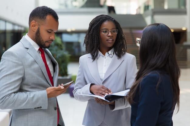Успешные разнообразные деловые люди обсуждают контракт