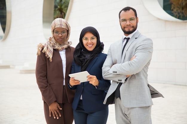 外でポーズのタブレットで成功した異人種間ビジネスチーム