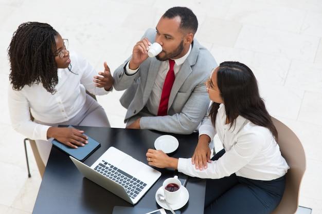 Разнообразные коллеги по бизнесу пьют кофе