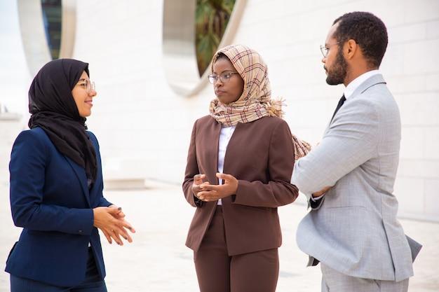 多様なビジネスパートナーが外で会議を行い、取引について話し合う