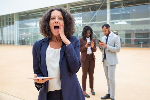 Взволнованная деловая женщина с планшетом получает отличные шокирующие новости