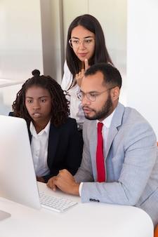 Возбужденные коллеги используют компьютер вместе
