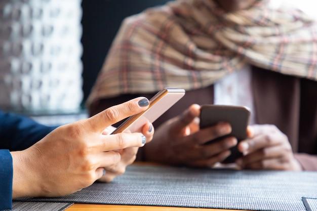 Женщины-коллеги общаются по телефону в кафе