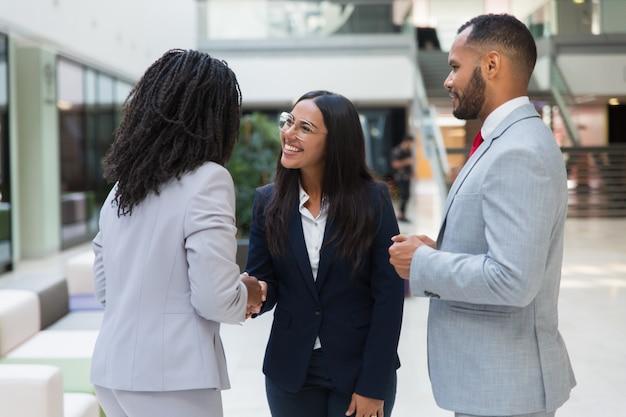 Женские разнообразные деловые партнеры пожимают друг другу руки