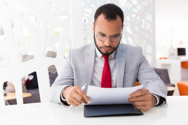 Сосредоточенный бизнесмен, читающий контракт