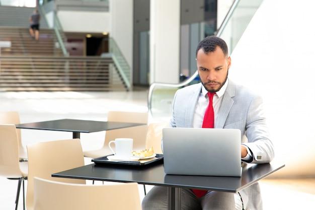 Сосредоточенный трудолюбивый бизнесмен работает над проектом