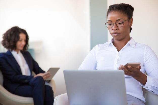 オフィスラウンジで働く若い女性マネージャーに焦点を当ててください。