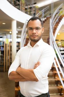Красивый черный человек позирует в публичной библиотеке