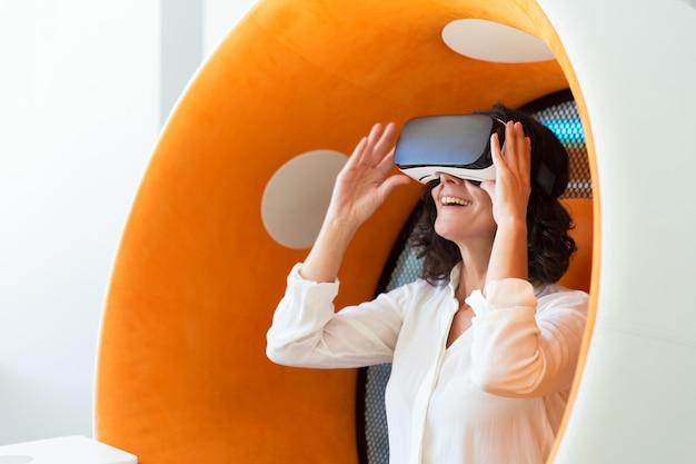 Счастливая коммерсантка наблюдая виртуальную презентацию