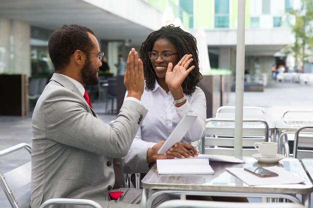 Счастливые коллеги по бизнесу радуются успеху команды