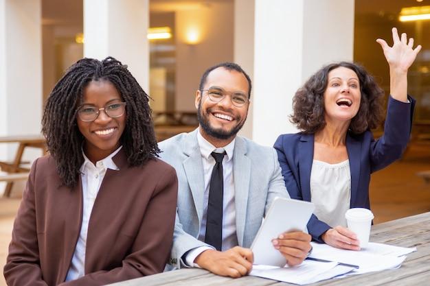 Счастливая команда дела приветствуя кого-то во время встречи